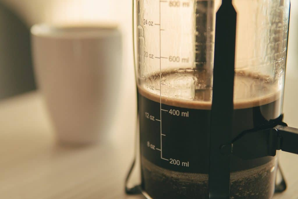 A french press with ounces to quarts conversion